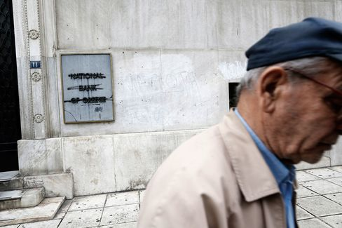 A pensioner passes a main branch of the National Bank of Greece in Thessaloniki.