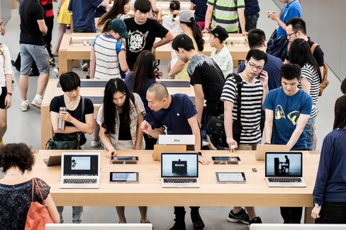 Customers look at laptops at Apple'snew Canton Road store in the Tsim Sha Tsui district of Hong Kong on July 30.