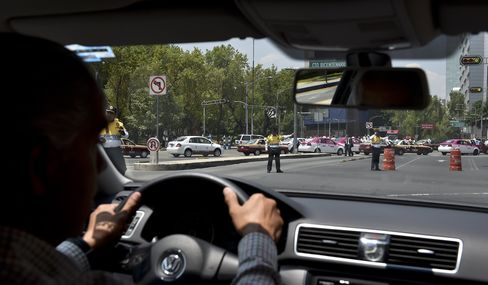An Uber driver is diverted by traffic police as taxi drivers cross the avenue during a protest against the company, in Mexico City, on May 25, 2015.