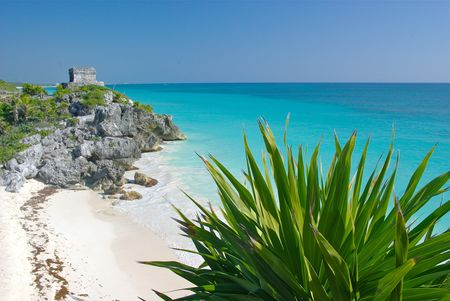 Mayan pyramid above a white sand beach and blue waters at Tulum, Mexico, south of Cancun.