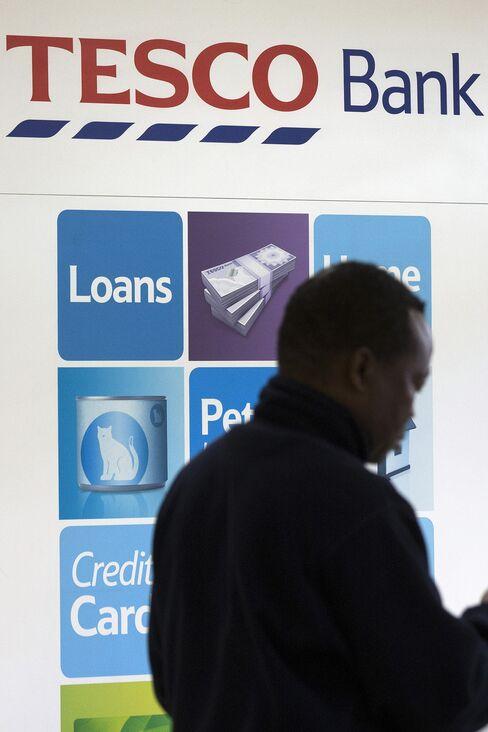 A Customer Passes an Advertisement for Tesco Bank