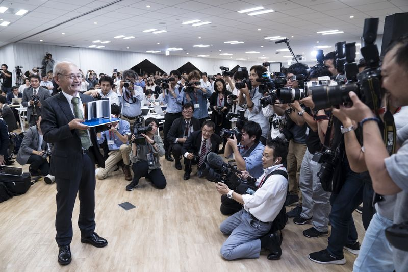 Akira Yoshino holds a model of a lithium-ion battery during a press conference on Oct. 9.