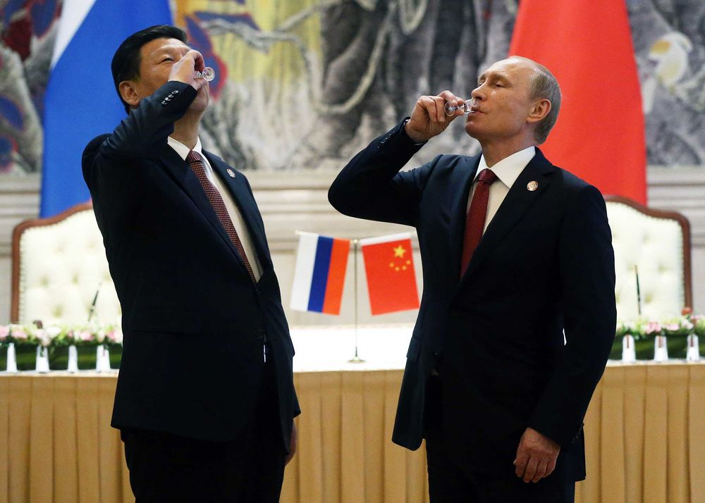 Chinese President Xi Jinping and Russian President Vladimir Putin toast with vodka during a signing ceremony on May 21, 2014, in Shanghai. Russia and China signed a 30-year contract for supply of gas.