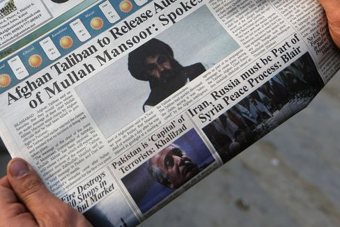 A man reads a newspaper in Kabul with a photo of the Afghan Taliban leader Mullah Mansour, center, in this Dec. 6, 2015 photo.