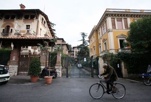 A cyclist rides a bicycle past the gates to a private residential street in the Coppede district of Rome, Italy, on Jan. 2, 2013.