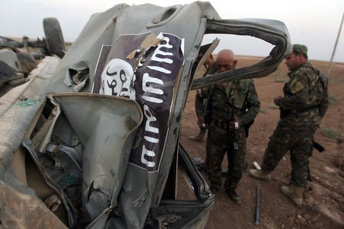 Peshmerga fighters inspect the remains of a car, bearing an image of the trademark jihadist flag, which belonged to Islamic State (IS) militants after it was targeted by an American air strike in the village of Baqufa, north of Mosul, on August 18, 2014.