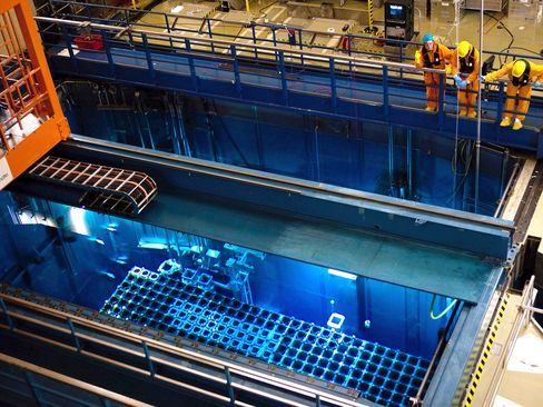 Employees adjust nuclear fuel rods in a fuel pool.