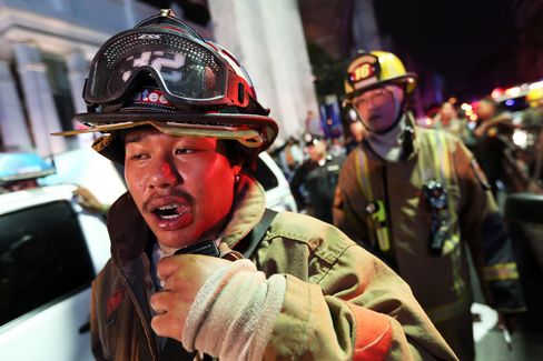 A member of the Fire Department radios to colleagues following an explosion at the Ratchaprasong intersection in Bangkok, Thailand, on Monday, Aug. 17, 2015. A powerful explosion struck Bangkok's central shopping district, with Thai police saying they suspect an improvised explosive device.