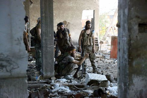 Rebel fighters speak during clashes with regime forces in Ramussa, Aleppo on Aug. 6.