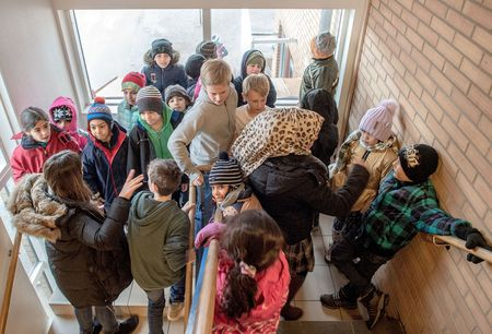 Swedish students walk through a group of refugee children.