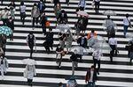 Pedestrians walk on a zebra crossing outside Shinjuku station in Tokyo
