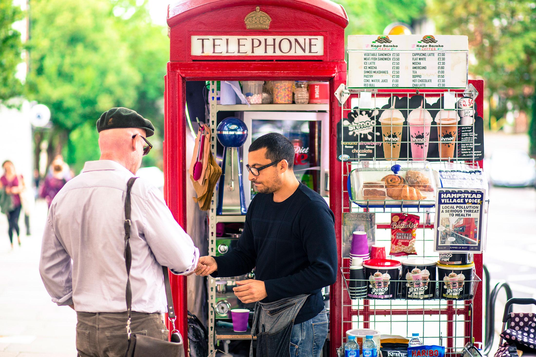 Umar Khalid, co-owner of the Kape Barako phone booth coffee stall, serves a customer.