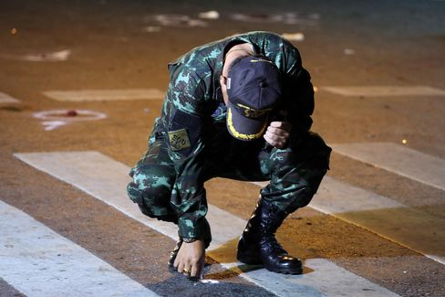 A Thai Army officer collects evidence in the street following an explosion at the Ratchaprasong intersection in Bangkok, Thailand, on Monday, Aug. 17, 2015. A powerful explosion struck Bangkok's central shopping district, with Thai police saying they suspect an improvised explosive device.