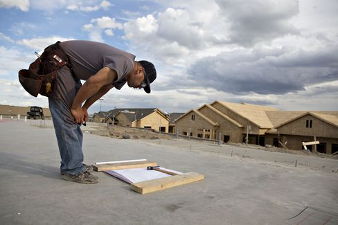 A worker looks over blueprints for a building under construction in Williston.