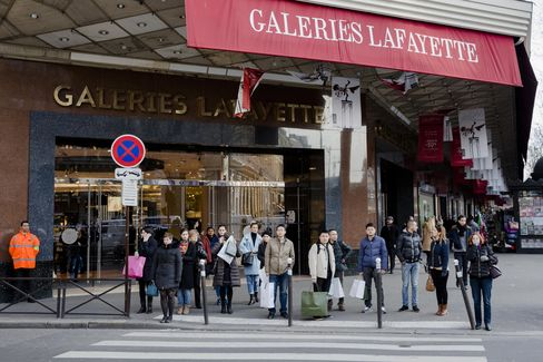 Shoppers wait to cross a road in front of a Galeries Lafayette department store in Paris, France, on Wednesday, Feb. 4, 2015. The European Commission is