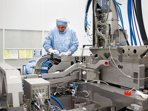 An employee assembles a photolithography machine at the ASML Holding NV factory in Veldhoven, Netherlands.