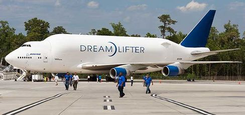 Boeing employees walk past the Dreamlifter, a huge custom cargo aircraft designed for transporting Boeing Dreamliner 787 fuselage sections to Boeing's new production facility on April 27, 2012, in North Charleston, S.C.