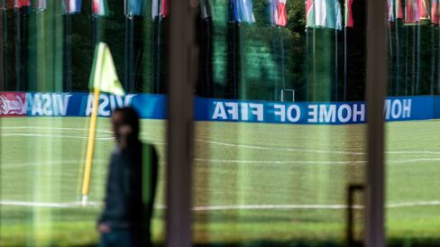 Flags of FIFA member nations are reflected on a glass panel outside FIFA's headquarters following the cancellation of a planned FIFA executive committee press conference in Zurich, Switzerland, on Sept. 25, 2015.