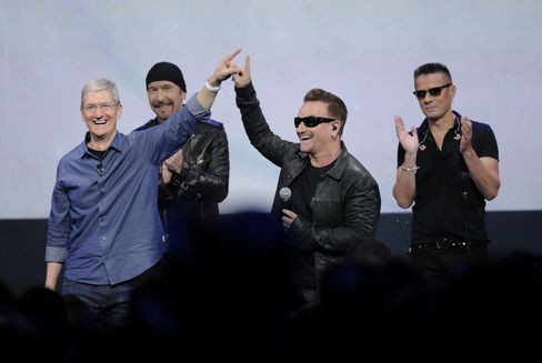 Apple CEO Tim Cook, left, and the band U2 gesture during a product announcement at Flint Center in Cupertino, California, on Sept. 9, 2014.