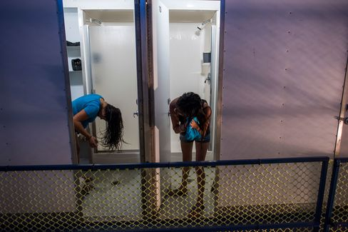 Two women dry their hair after taking showers at the portable showers available to use for free at the Iglesia Emmanuel Church in Porterville, Calif., on April 13, 2015. In a handful of drought-plagued communities, including Cambria, East Porterville and Santa Cruz, scarcity has forced changes. The communities face especially strict limits because they aren't part of the State Water Project, a system of canals and reservoirs that delivers mountain runoff to urban areas in the Bay Area and Southern California.
