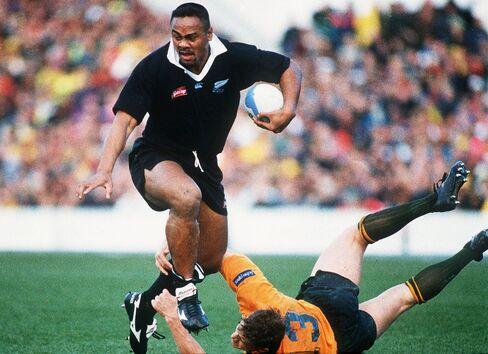 All Black Jonah Lomu slips the tackle of Australia