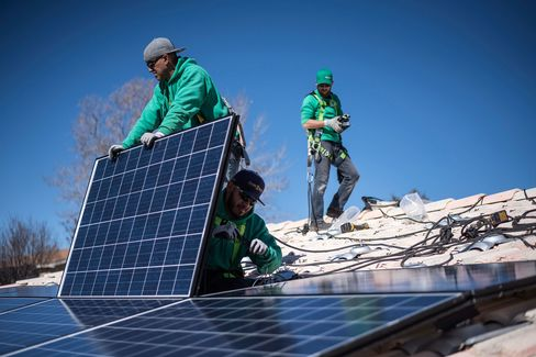 Workers secure solar panels to a rooftop during a SolarCity Corp. residential installation.