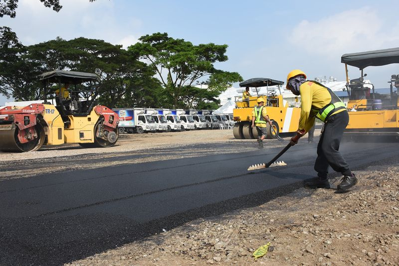 Workers lay a road made with asphalt and recycled plastics at a test site near Manila. Image: San Miguel Corp.