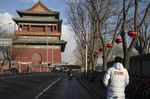 A pedestrian walks along a road past the Drum Tower in Beijing.