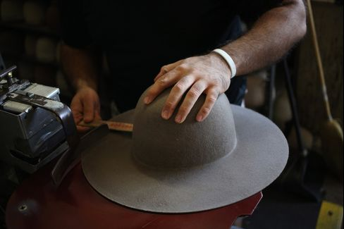 A worker uses her hands to help sand and smooth a Stetson brand cowboy hat during production at the Hatco Inc. manufacturing facility in Garland, Texas, U.S.