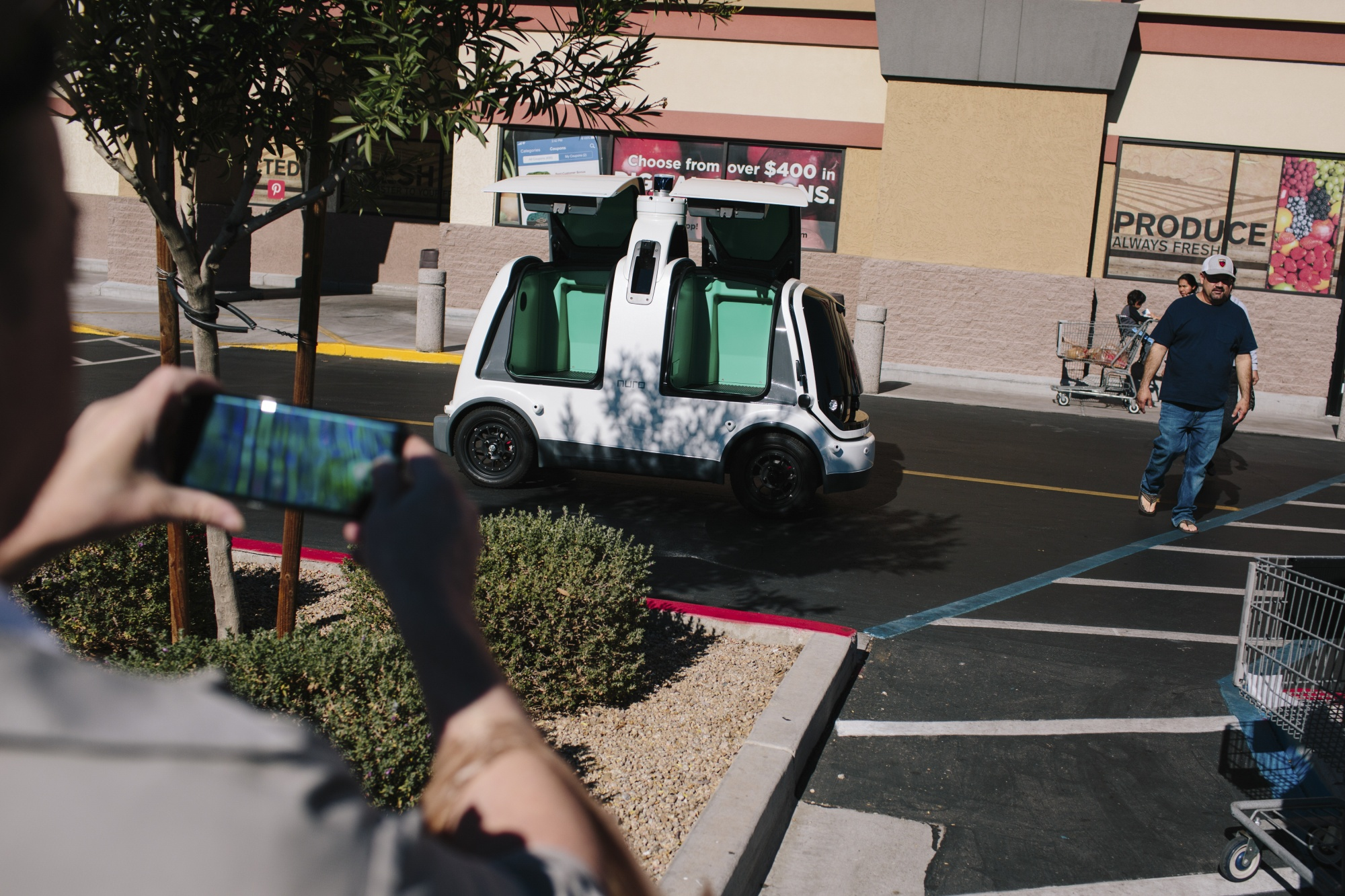 Shoppers photograph a Nuro mini car, which is a self-driving vehicle, outside Fry's Food Store in Scottsdale, Ariz.