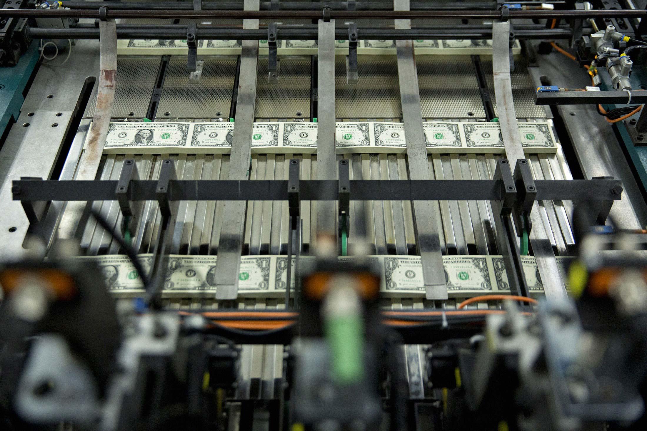 Tumpukan uang kertas $ 1 bertuliskan nama Menteri Keuangan AS Steven Mnuchin bergerak melalui mesin di Biro Ukiran dan Pencetakan A.S. di Washington, D.C., A.S., pada hari Rabu, 15 November 2017
