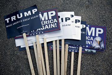 Campaign signs for Donald Trump, president and chief executive of Trump Organization Inc. and 2016 Republican presidential candidate, sit on the ground before a campaign rally at Pennichuck Middle School in Nashua, New Hampshire, U.S., on Monday, Dec. 28, 2015. Trump urged supporters at a New Hampshire rally to get to the polls, saying he needs the big crowds he's drawing to translate into votes. Photographer: Andrew Harrer/Bloomberg
