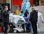 A body wrapped in plastic that was unloaded from a refrigerated truck is handled by medical workers wearing personal protective equipment due to COVID-19 concerns, Tuesday, March 31, 2020, at Brooklyn Hospital Center in Brooklyn borough of New York. The body was moved to a hearse to be removed to a mortuary. The new coronavirus causes mild or moderate symptoms for most people, but for some, especially older adults and people with existing health problems, it can cause more severe illness or death. (AP Photo/John Minchillo)