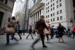 Pedestrians pass in front of the New York Stock Exchange (NYSE).