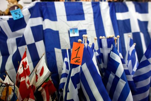 Greek national flags with a one euro price tag sit for sale at a Euro store in Athens, Greece.