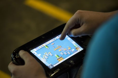 An attendee uses a game console to create a new level of Super Mario Maker during a hackathon at the Facebook headquarters in Menlo Park, Calif., on July 29, 2015.