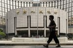 A pedestrian walks past the People's Bank of China (PBOC) headquarters in Beijing, China.