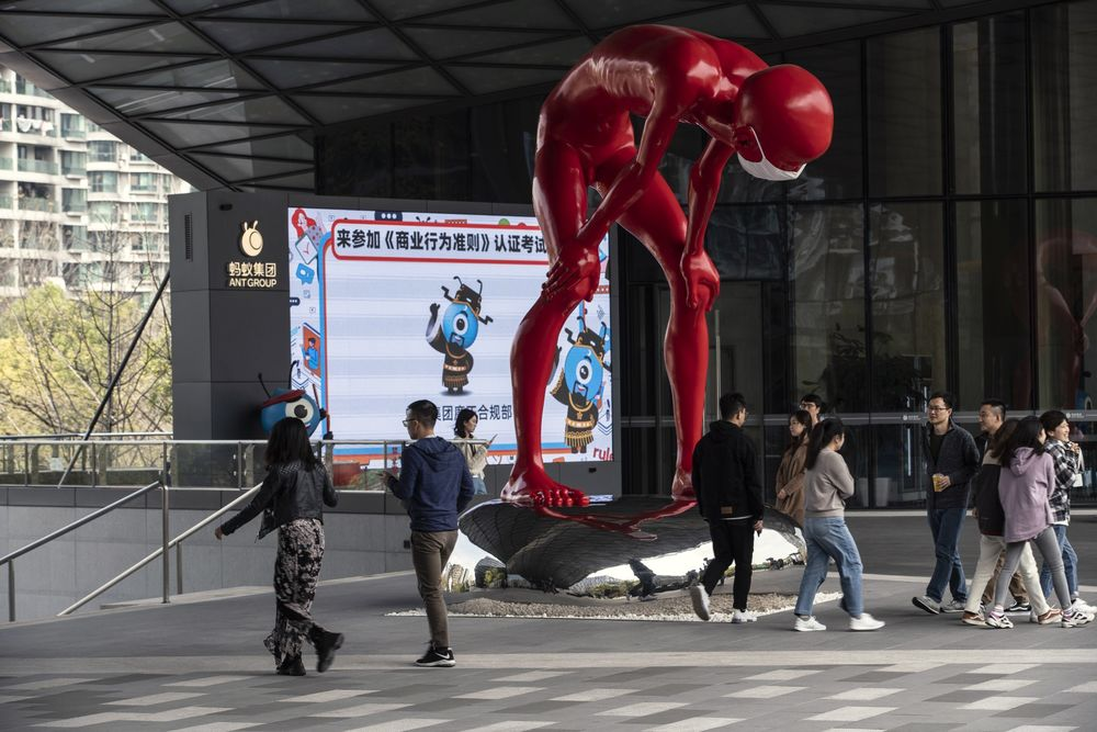 People walk past a sculpture by artist Chen Wenling at the Ant Group Co. headquarters in Hangzhou.