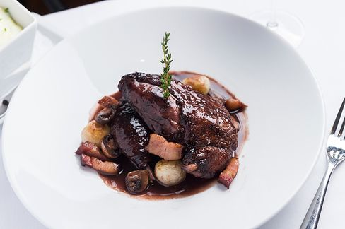 A classic coq au vin, or chicken braised in red wine, with a thoroughly old-fashioned garnish: a sprig of thyme.
