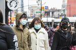Pedestrians wearing face masks walks along a street in the Flushing neighborhood in the Queens Borough of New York, U.S.