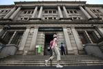 A pedestrian walks past the Bank of Japan headquarters in Tokyo, Japan.