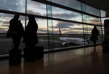 Passengers stand by a window as they wait to board a Ryanair Holdings Plc aircraft at Dublin Airport, operated by Dublin Airport Authority, in Dublin, Ireland, on Friday, Nov. 25, 2016. Ryanair provides low fare passenger airline services to destinations in Europe. Photographer: Chris Ratcliffe/Bloomberg