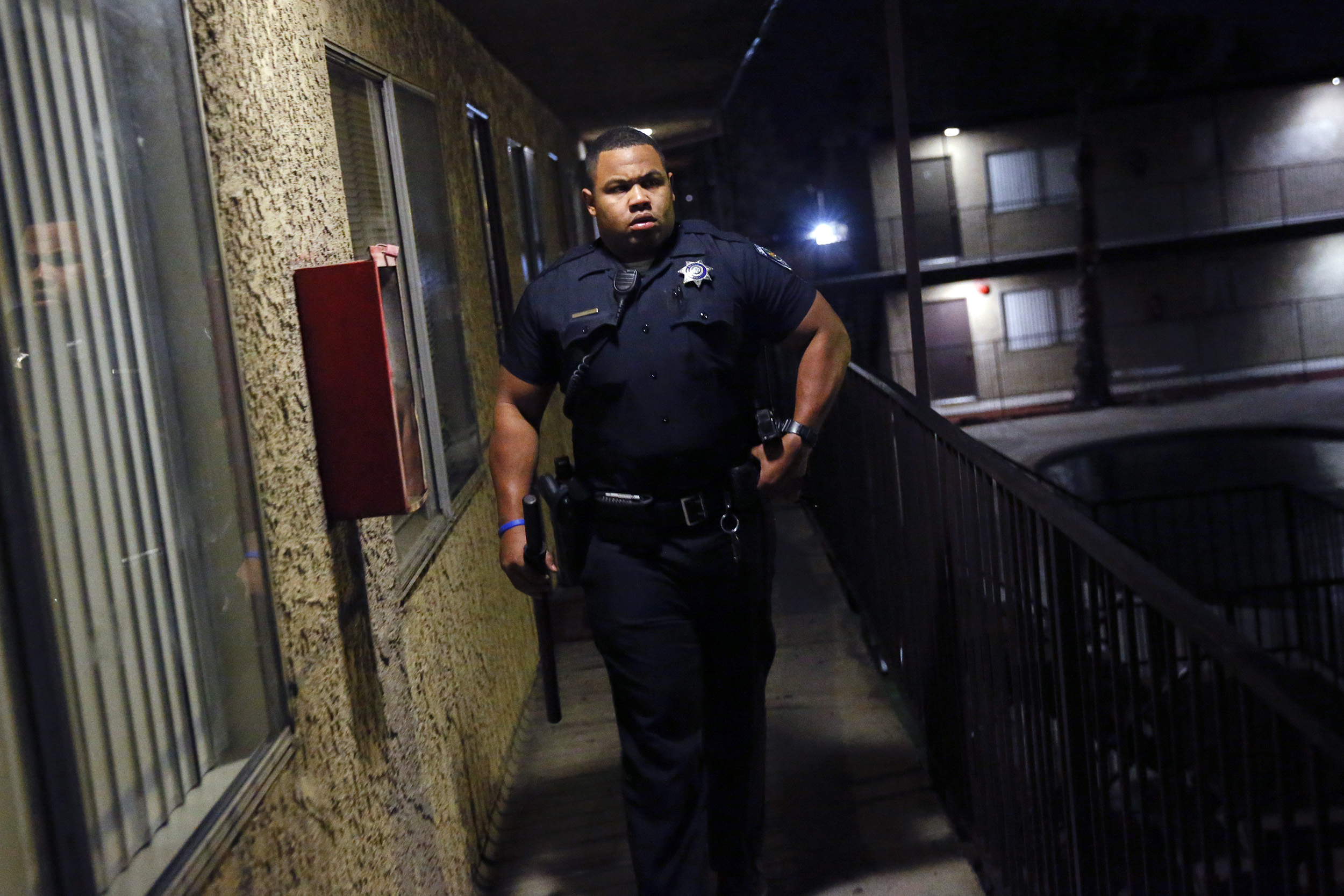 San Bernardino Police Department Officer Darren Sims walks through an apartment complex after providing assistance to a fire department response to a false medical 911 call on the graveyard shift in San Bernardino, California, U.S., on Saturday, January 24, 2015.