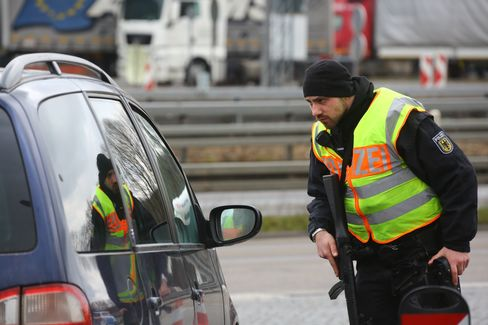 A police officer checks a car at the border between Germany and Belgium