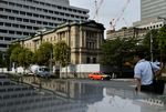 Pedestrians walk past the Bank of Japan (BOJ) headquarters in Tokyo, Japan, on Wednesday, Sept. 13, 2017. The BOJ's next monetary policy meeting is scheduled for Sept. 21. The central bank pushed back in July the projected timing for reaching its 2 percent inflation target for the sixth time as economic growth failed to drive price gains.
