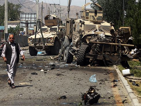 Damaged armored vehicles at the site of a blast targeting a NATO convoy in Kabul, on June 30, 2015.