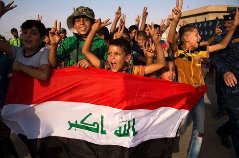 モスル解放に国旗を持って喜ぶ子供たち(9日)