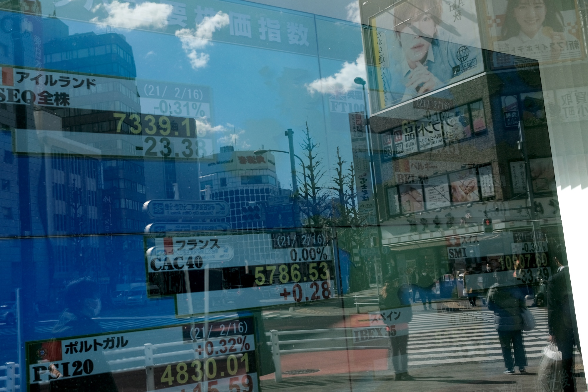 Buildings and pedestrians reflected on an electronic stock board outside a securities firm in the Shinjuku district of Tokyo, Japan, on Wednesday, Feb. 17, 2021. A surge in Japanese shares this week has pushed the Nikkei 225 past the 30,000 level for the first time since 1990.