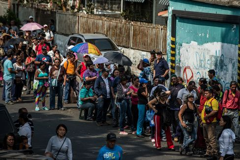 People wait in line outside of a grocery store in Caracas. Photographer: Meridith Kohut/Bloomberg