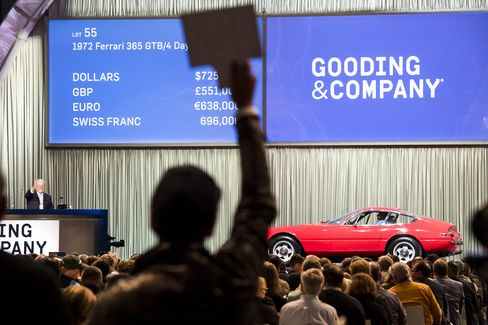 A bidder holds up a paddle as he bids for a 1972 Ferrari 365 GTB/4 Daytona during the Gooding & Company auction on Saturday, Aug. 20, 2016.
